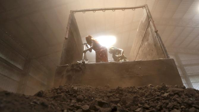 File photo of workers unloading coal from supply truck at a yard on the outskirts of western city of Ahmedabad