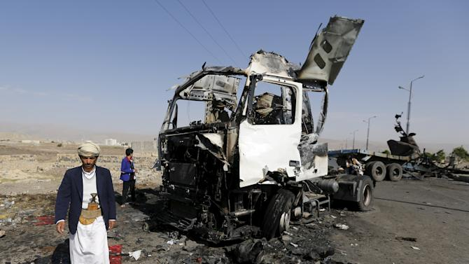 A man walks past a truck hit by a Saudi-led air strike in Yemen's northwestern province of Amran