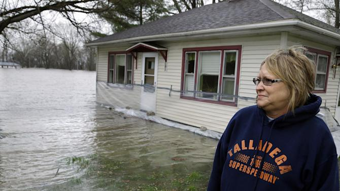 Jeanette Bricker watches the Illinois River rises out of it's banks surrounding and flooding her home Tuesday, April 23, 2013, in Spring Bay Ill. Floodwaters are rising to record levels along the Illinois River in central Illinois.  . (AP Photo/Seth Perlman)