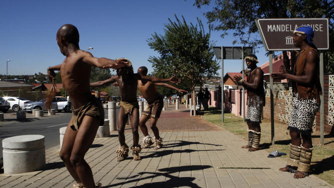 In this photo taken Tuesday April 23, 2013 traditional dancers perform close to the old Mandela home turned museum, unseen, in Vilikazi street, the tourist hub of Soweto, South Africa.   Mandela, now old and frail, lives in seclusion in his Johannesburg home. Beyond the high walls of the house. the fightng over his image and what he stood for has already begun.  (AP Photo/Themba Hadebe)