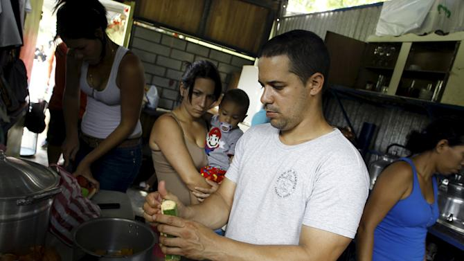 Cuban migrant Boza peels a plantain as his wife Silenay holds their 10 month-old son Yeryko at the kitchen of a shelter in Liberia