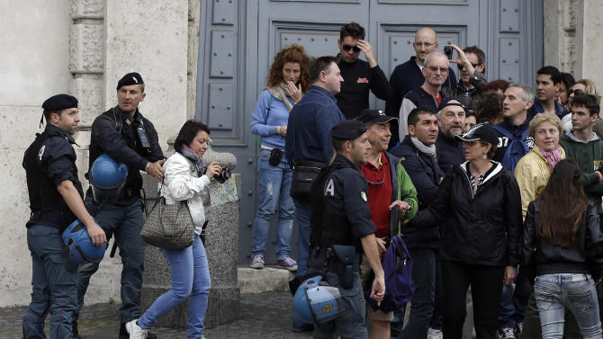 Police officers move people from the square near Quirinale's presidential palace in Rome, Saturday, April 27, 2013. Italy appeared poised Saturday to finally get a new government, a broad coalition which brings media mogul Silvio Berlusconi's forces back to power, this time in tense alliance with center-left rivals. Premier-designate Enrico Letta arrived at the Quirinale Palace to brief Italy's president, a meeting widely seen as indicating the center-left leader either had succeeded, or was on the verge of succeeding, in forming a government commanding strong support in Parliament. (AP Photo/Gregorio Borgia)