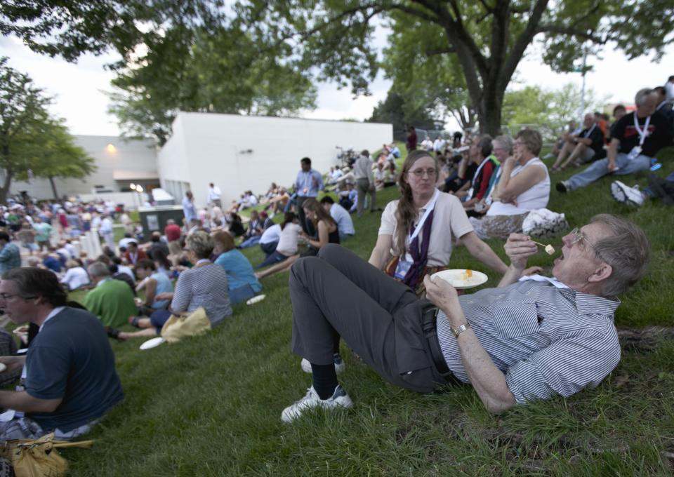Phil Martin of Minneapolis is watched by his wife Linda as he snacks with other shareholders outside the Berkshire-owned Borsheims jewelry store in Omaha, Neb., Friday, May 4, 2012. Berkshire Hathaway is expected to have 30,000 shareholders come to Omaha for it's annual shareholders meeting this weekend. (AP Photo/Nati Harnik)