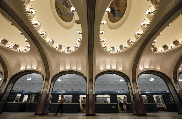 A woman walks on the platform as a train arrives at Mayakovskaya metro station, which was built in 1938, in Moscow