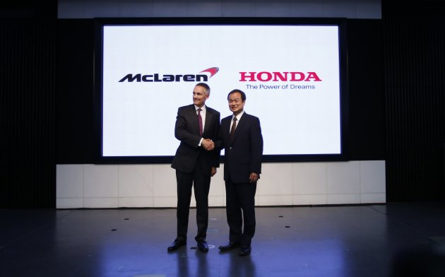 Honda Motor Co's President and CEO Ito shakes hands with McLaren Group Limited CEO Whitmarsh at their joint news conference in Tokyo