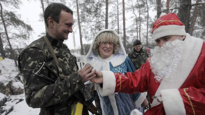 Volunteers from Kharkiv dressed as Father Frost and his granddaughter Snegurochka give a gift to a Ukrainian serviceman outside Lugansk