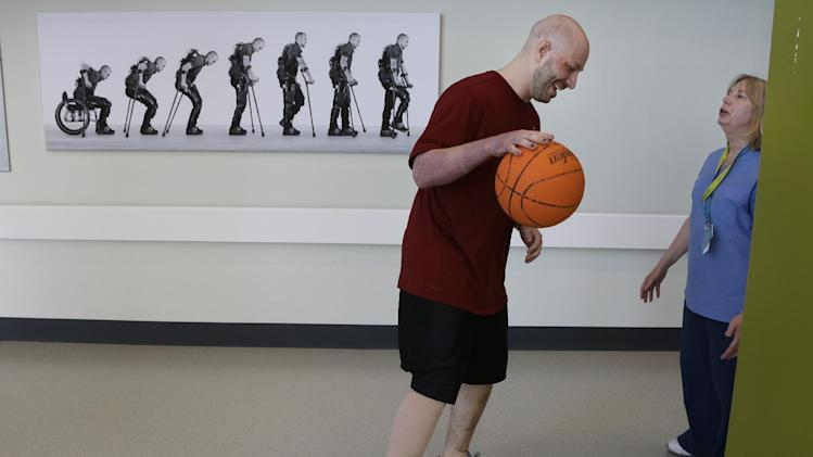 Boston Marathon bombing victim James Costello dribbles a basketball under the guidance of Physical Therapist Lisa Pratt at Spaulding Rehabilitation Hospital in Boston's Charlestown section, Friday, May 10, 2013. (AP Photo/Elise Amendola)