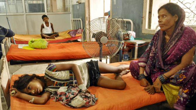An Indian woman sits beside a child who fell sick after eating a free school lunch, at a hospital in Patna, India, Thursday, July 18, 2013. Indian officials say at least 22 children have died and more than two dozen others were sickened after eating a free school lunch that was tainted with insecticide. India's midday meal scheme is one of the world's biggest school nutrition programs, covering some 120 million school children. (AP Photo/ Aftab Alam Siddiqui)
