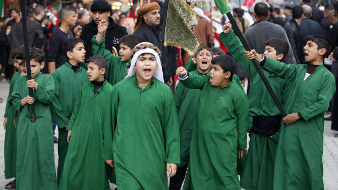 Children re-enact the role of companions to Imam Hussein during the battle of Karbala, at the Imam Moussa al-Kadhim shrine during the festival of Ashoura in Baghdad, Iraq, Saturday, Nov. 24, 2012. Ashoura marks the anniversary of the battle of Karbala when Imam Hussein, a grandson of Prophet Muhammad, was killed. (AP Photo/Karim Kadim)