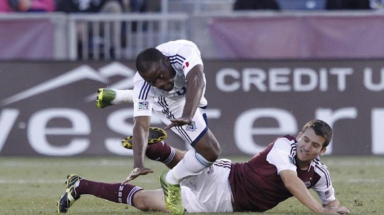 Vancouver Whitecaps midfielder Nigel Reo-Coker, top, is tripped up by Colorado Rapids midfielder Nathan Sturgis in the second half of the Rapids' 3-2 victory in a MLS soccer game in Commerce City, Colo., on Saturday, Oct. 19, 2013