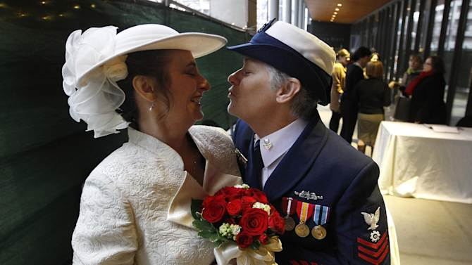 Retired U.S. Coast Guard Petty Officer 1st Class Nancy Monahan, right, wears her dress uniform as she leans to kiss her soon-to-be bride Deb Needham while they wait at Seattle City Hall to become among the first gay couples to legally wed in the state, Sunday, Dec. 9, 2012, in Seattle. The couple is from Renton, Wash. Gov. Chris Gregoire signed a voter-approved law legalizing gay marriage Dec. 5 and weddings for gay and lesbian couples began in Washington on Sunday, following the three-day waiting period after marriage licenses were issued earlier in the week. (AP Photo/Elaine Thompson)