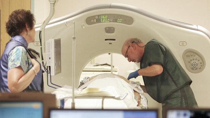 FILE - In this June 3, 2010, file photo, Dr. Steven Birnbaum works with a patient in a CT scanner at Southern New Hampshire Medical Center in Nashua, N.H. A national study suggests the world's top cancer killer isn't always as deadly as doctors once thought, finding that more than 18 percent of lung cancers detected in screening scans are likely so slow growing that they'd never cause problems. But the provocative results are unlikely to change how doctors treat lung cancer. (AP Photo/Jim Cole, File)