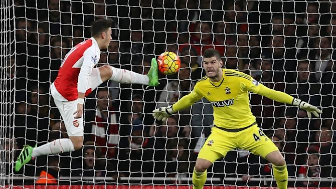 Arsenal's Mesut Ozil (L) fails to score past Southampton 'keeper Fraser Forster during their English Premier League match at the Emirates Stadium