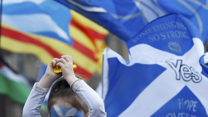 A girl with a Saltire painted on her face sits on an adult's shoulders at a Scottish National Party rally in Glasgow