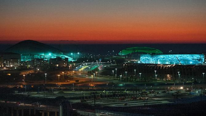 In this Thursday, Oct. 24, 2013, file photo, the Bolshoi Ice Dome, background center, Iceberg skating arena, right, and the Fisht Olympic Stadium, left, are illuminated at night in Sochi, Russia. Sochi will host the 2014 Winter Olympic Games next month