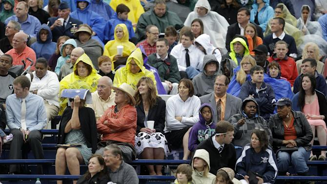 Guests sit in the stands in the the rain showers at the commencement ceremony for the United States Naval Academy in Annapolis, Md., Friday, May 24, 2013, where President Barack Obama addressed the graduates. (AP Photo/Pablo Martinez Monsivais)
