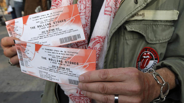 "Rolling Stones fan who named himself as Patrice, 55, and who claims he has seen 54 Rolling Stones concerts, shows the tickets he bought for tonight's concert in Paris, Thursday, Oct. 25, 2012. The Rolling Stones announced a surprise ""warm-up gig"" in Paris, and within an hour the Champs Elysees was swarming with fans hoping to get satisfaction with one of the 350 tickets for the Thursday night show. (AP Photo/Francois Mori)"