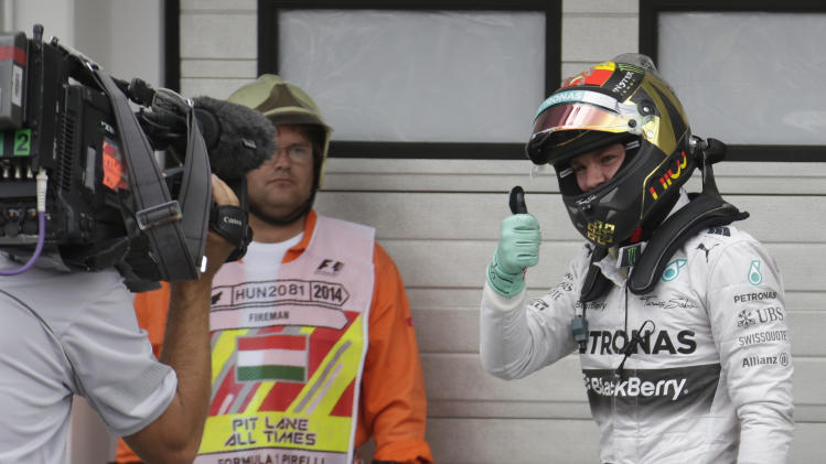 Mercedes driver Nico Rosberg of Germany gives thumb up after he clocked the fastest time during the qualifying of the Hungarian Formula One Grand Prix in Budapest, Hungary, Saturday, July 26, 2014. The Hungarian Grand Prix will be held on Sunday, July 27, 2014. (AP Photo/Petr David Josek)