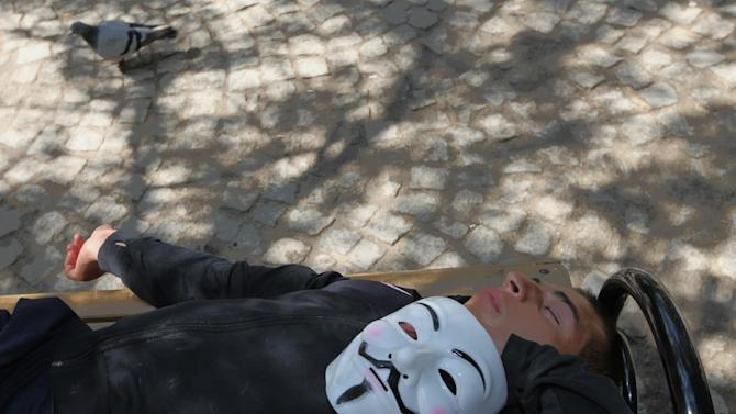 A Turkish protester sleeps in Kugulu Park in Turkish capital, Ankara, Monday, June 10, 2013. In a series of increasingly belligerent speeches to cheering supporters Sunday, Turkey's prime minister Recep Tayyip Erdogan launched a verbal attack on the tens of thousands of anti-government protesters who flooded the streets for a 10th day, accusing them of creating an environment of terror. (AP Photo/Burhan Ozbilici)