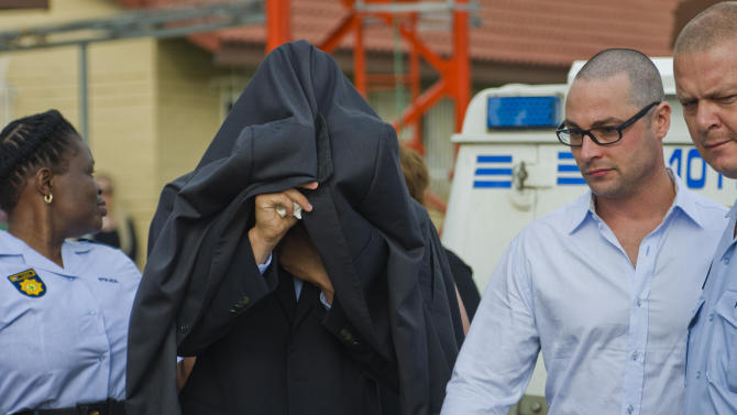 Oscar Pistorius, centre,  is led from the Boschkop police station east of Pretoria,  en route to court, Friday Feb. 15, 2012. Oscar Pistorius arrived at a courthouse Friday, for his bail hearing in the murder case of his girlfriend as South Africans braced themselves for the latest development in a story that has stunned the country. The Paralympic superstar was earlier seen leaving a police station in a dark suit with a charcoal gray jacket covering his head as he got into a police vehicle. Model Reeva Steenkamp was shot and killed at Pistorius' upmarket home in an eastern suburb of the South African capital in the predawn hours of Thursday. (AP Photo)