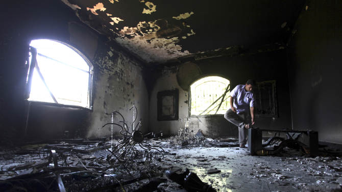 FILE - In this Sept. 13, 2012 file photo, a Libyan man investigates the inside of the  U.S. Consulate, after an attack that killed four Americans, including Ambassador Chris Stevens on the night of Tuesday, Sept. 11, 2012, in Benghazi, Libya. U.S. officials tell The Associated Press that the CIA station chief in Libya reported to Washington within 24 hours of last month's deadly attack on the U.S. Consulate that there was evidence it was carried out by militants, not a mob upset about an American-made, anti-Muslim movie. It is unclear whether anyone outside the CIA saw the cable at that point or how high up in the CIA the information went. (AP Photo/Mohammad Hannon, File)