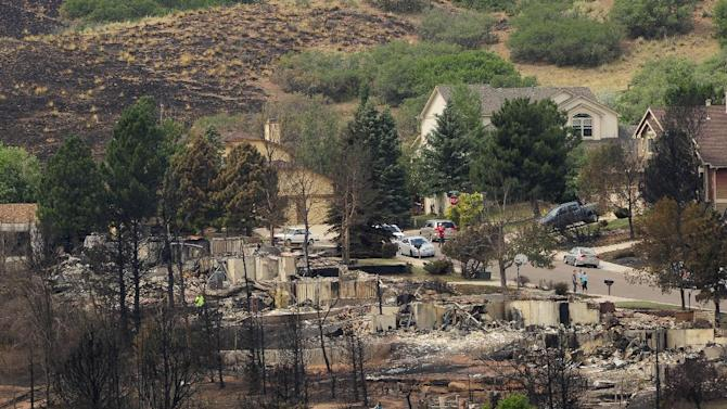 Residents of the Mountain Shadows area view their properties on Sunday, July 1, 2012, in Colorado Springs, Colo. Even people who know their homes are still standing have some anxiety over temporary visits being allowed today to wildfire-devastated neighborhoods around Colorado Springs. About 10,000 people are still out of their homes, having been among 30,000 who initially fled the most destructive fire in Colorado's history.(AP Photo/The Colorado Springs Gazette, Susannah Kay)