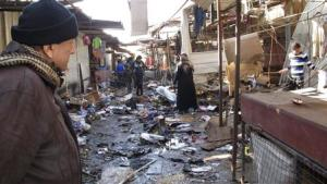 A man looks at the site of bomb attack at a marketplace…