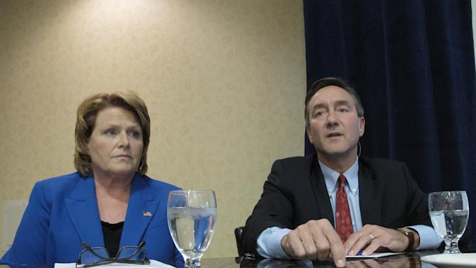 FILE - In this Oct. 11, 2012, file photo, Democratic Senate candidate Heidi Heitkamp, left, listens to Republican opponent Rick Berg, right, speak at a North Dakota Chamber of Commerce forum on health care and energy at a hotel in Bismarck, N.D. North Dakota's competitive Senate race is coming down to ticket splitters. Republican presidential hopeful Mitt Romney is expected to easily win the state, which is now enjoying a boom in energy development. But in the race for retiring Democrat Kent Conrad's seat in the U.S. Senate, GOP Congressman Berg is locked in a bitter battle with the state's former Democratic attorney general, Heitkamp. (AP Photo/Dale Wetzel, File)
