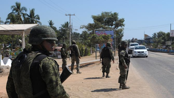 Navy marines stand at a roadblock due to stepped up security after masked armed men broke into a beach home, raping six Spanish tourists who had rented the house in Acapulco, Mexico, Tuesday Feb. 5, 2013. According to the Mayor of Acapulco, five masked men burst into a house the Spaniards had rented on the outskirts of Acapulco, in a low-key area near the beach, and held a group of six Spanish men and one Mexican woman at gunpoint, while they raped the Spanish women before dawn on Monday. (AP Photo/Bernandino Hernandez)