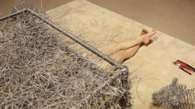 Chinese artist Zhou lies under an unfinished iron wire bed as she tries to look at her work from another angle at Beijing Art Now Gallery, in Beijing
