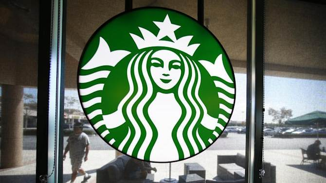 A Starbucks logo hangs on a window at a newly designed Starbucks coffee shop in Fountain Valley