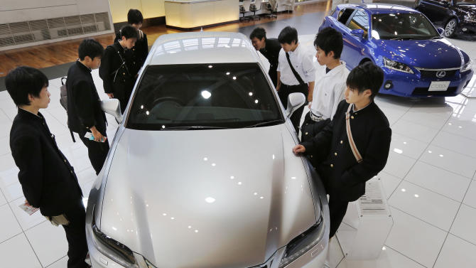 School boys look at a Lexus GS450h displayed at the Toyota Motor Corp. showroom Toyota Mega Web in Tokyo Wednesday, May 8, 2013. Toyota's January-March profit more than doubled to 313.9 billion yen ($3.2 billion) as cost cuts and better sales worked with a weakening yen to add momentum to the automaker's comeback. (AP Photo/Itsuo Inouye)