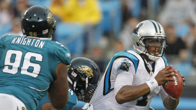 Carolina Panthers' Cam Newton (1) scrambles as Jacksonville Jaguars' Jeremy Mincey (94) garbs his jersey during the second quarter of an NFL football game in Charlotte, N.C., Sunday, Sept. 25, 2011. (AP Photo/Bob Leverone)