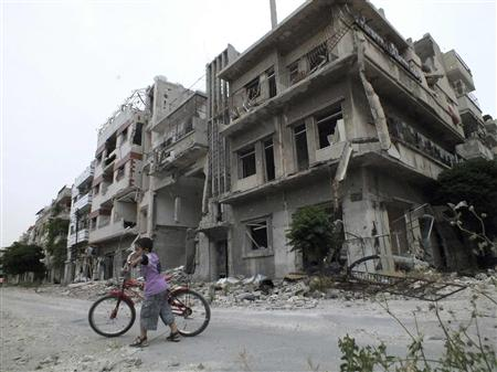 A boy rides a bicycle in front of damaged buildings in Homs