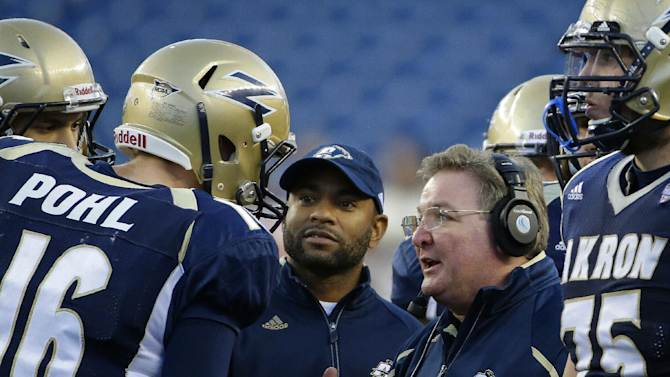 Akron head coach Terry Bowden, second from right, has a conversation with quarterback Kyle Pohl (16) during a fourth quarter timeout of an NCAA college football game against Massachusetts in Foxborough, Mass., Saturday, Nov. 16, 2013. Akron defeated Massachusetts 14-10