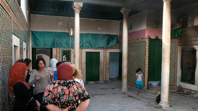 Women talk in the courtyard after masked individuals  attacked and set fire to the popular 500-year-old  Manouba shrine  in Manouba west of Tunis, early Tuesday, Oct. 16, 2012. The shrine, which serves as a refuge for poor women, is also a place of symbolic worship for many Tunisians who visit the shrine bringing along food, money and candles. (AP Photo/Amine Landoulsi)