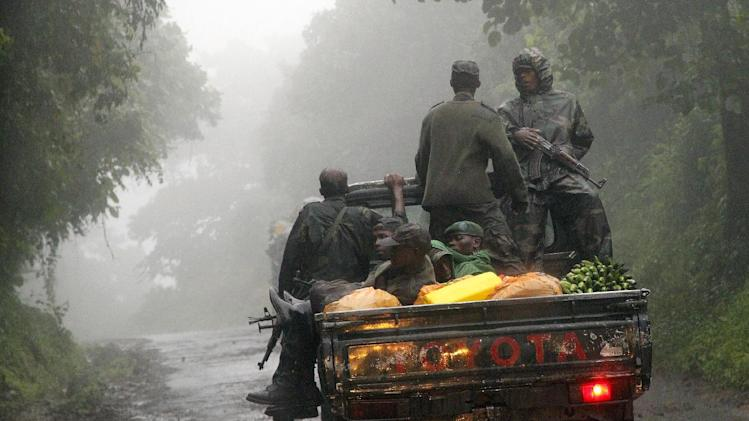 Congolese M23 rebels carry goods in the back of a truck  near the Congo-Uganda border town of Bunagana Wednesday Dec. 5 2012. Speaking to the Associated Press,  M23 president Jean Marie Runiga  said they would not accept for the Kinshasa government to pay the M23 expenses at the scheduled Kampala talks later this week, as the two are still in a belligerent state. M23 rebels completed their withdrawal from the strategic eastern city of Goma  on Saturday, in compliance with an agreement reached between the rebel group and a regional body, they could still be seen in positions three kilometers from Goma airport. (AP Photo/Jerome Delay)