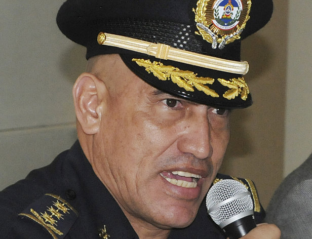 "FILE - In this May 22, 2012 file photo, officer Juan Carlos Bonilla Valladares, known as ""El Tigre"" or ""The Tiger"" speaks to the press after he was sworn-in as Honduras' new Chief of Police in Tegucigalpa, Honduras. The U.S. government is withholding funds to Honduran law enforcement units directly supervised by their new national police chief until the U.S. can investigate allegations that he ran a death squad a decade ago, according to a State Department report released in August 2012. (AP Photo/Fernando Antonio, File)"