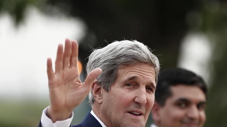 U.S. Secretary of State Kerry waves towards the media upon his arrival at the airport in New Delhi