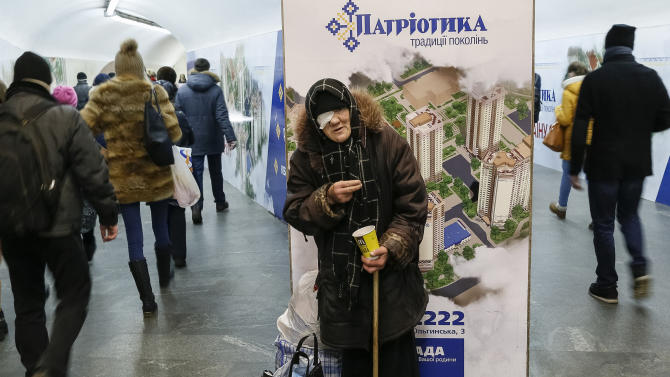 An elderly woman begs for money at a subway underpass in Kiev
