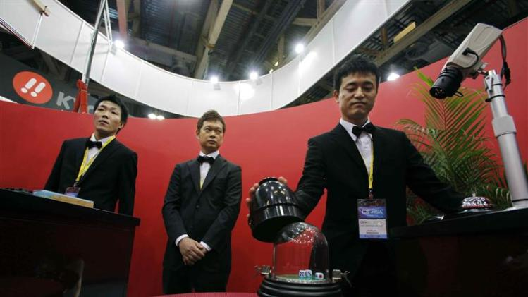 File photo of croupiers operating a dice game monitored by a surveillance camera at Global Gaming Expo Asia in Macau