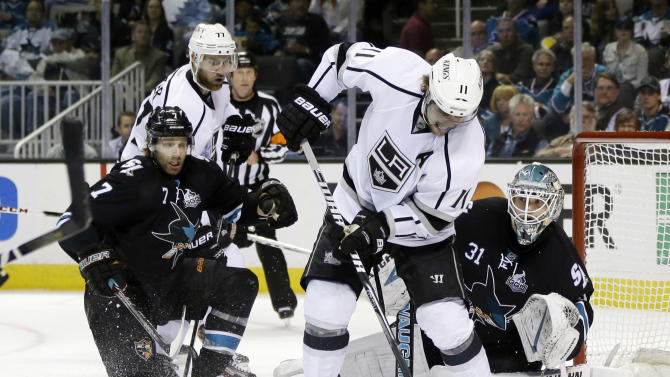 Los Angeles Kings center Anze Kopitar, center, of Slovenia, controls the puck next to San Jose Sharks goalie Antti Niemi, of Finland, right, teammate Jeff Carter (77) and the Sharks' Brad Stuart (7) during the second period in Game 4 of their second-round NHL hockey Stanley Cup playoff series in San Jose, Calif., Tuesday, May 21, 2013. (AP Photo/Marcio Jose Sanchez)