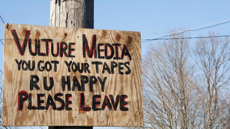 A sign expressing displeasure with the media is tacked on a pole in Newtown