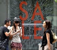 Shoppers walk in front of a large sale sign in Tokyo. Japan's prime minister looks set to survive a no-confidence motion after reaching an 11th hour deal with a major opposition party over his much-cherished sales tax bill