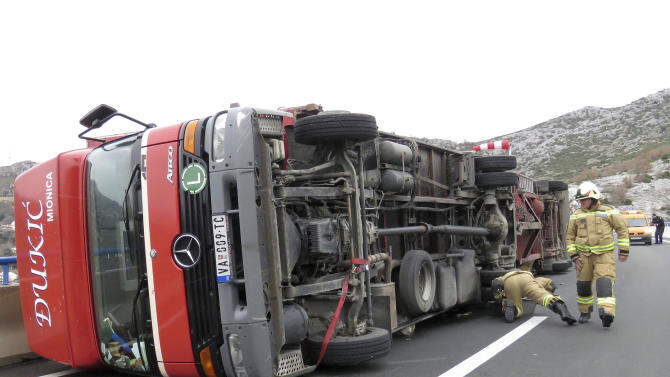 Firemen inspect a truck overturned by heavy winds, near Split, Croatia, Thursday, March 5, 2015. Winds caused traffic disruptions in much of coastal Croatia. (AP Photo/Ivo Cagalj, PIXSELL)