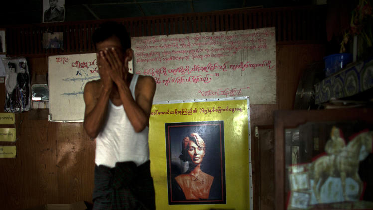 In this Sept. 1, 2012 photo, an HIV patient rubs his face near a poster showing a sculpture of the Nobel Peace Prize laureate Aung San Suu Kyi at an HIV/AIDS center founded by a member of Myanmar's opposition party National League for Democracy, led by Suu Kyi, on the outskirts of Yangon. Following a half century of military rule, care for HIV/AIDS patients in Myanmar lags behind other countries. Half of the estimated 240,000 people living with the disease are going without treatment and 18,000 are dying from it every year. (AP Photo/Alexander F. Yuan)