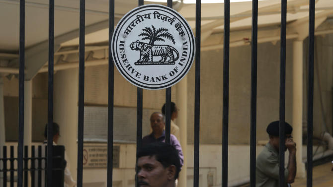 People walk near a logo of the Reserve Bank of India (RBI) displayed on the gate of the RBI headquarters in Mumbai, India, Tuesday, Oct. 29, 2013. India's central bank raised its key interest rate for the second time in two months, underlining its determination to control inflation despite concerns economic growth could slow further.(AP Photo/Rafiq Maqbool)