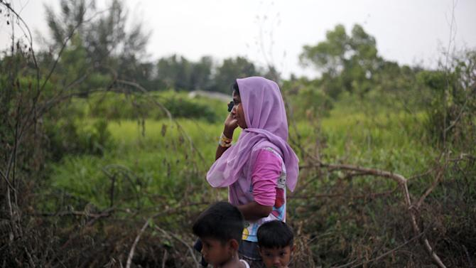 In this Thursday, May 21, 2015 photo, Rohingya migrant Satera Begum makes a phone call to her husband who resides in Malaysia, at a temporary shelter in Langsa, Aceh province, Indonesia. Thousands of migrants - about half of them Bangladeshi and the others minority Rohingya Muslims from Myanmar - have landed ashore in Indonesia, Malaysia and Thailand since May 10. (AP Photo/Binsar Bakkara)