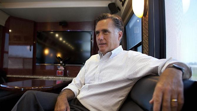 "FILE -In this June 8, 2012 file photo, Republican presidential candidate, former Massachusetts Gov. Mitt Romney talks with his staff while riding on his bus after a campaign stop in Council Bluffs, Iowa. Keeping his secrets, Romney tends to lift the veil on his finances and campaign only if the law says he must. The Republican presidential candidate refuses to identify his biggest donors who ""bundle"" money for his campaign. He often declines to say who meets with him. He puts limits on media access to his fundraisers. And he resists releasing all of his tax returns, making just a single year public after facing pressure to do so. He says he gives out all the information that's required by law. (AP Photo/Evan Vucci, File)"