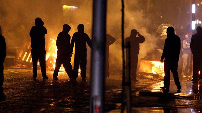 ADDS DATE - Loyalists set up burning barricades on the Newtownards Road in Belfast, Monday, Jan. 7, 2013, a month after the City Council decided to fly the union flag on designated days only. Protesters have been out in force — with sometimes violent results — since a Dec. 3 decision by Belfast City Council to stop flying the British flag year-round. Such issues of symbolism frequently inflame sectarian passions in Northern Ireland, where Protestants mainly want to stay in the United Kingdom and Catholics want to unite with the Republic of Ireland. (AP Photo/PA, Paul Faith)  UNITED KINGDOM OUT  NO SALES  NO ARCHIVE  PRESS ASSOCIATION Photo. Picture date: Monday January 7, 2013. See PA story ULSTER Protests. Photo credit should read: Paul Faith/PA Wire